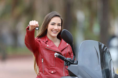 Happy motorcycle buyer showing keys at camera outdoor