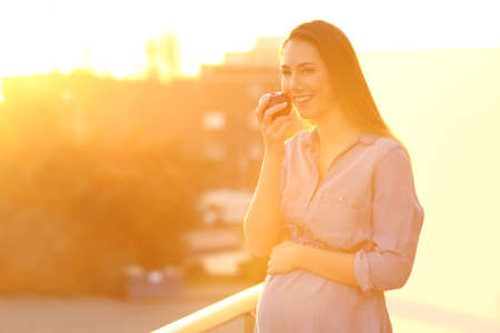 Pregnant woman holding an apple and looking at you in a balcony at sunset Reklamní fotografie