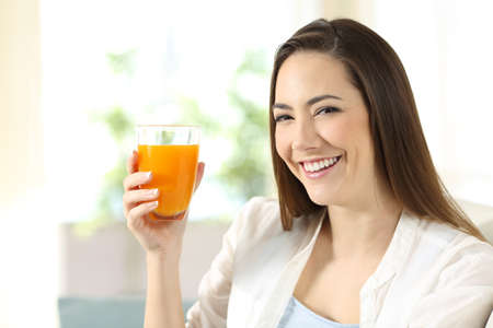 Portrait of a beautiful woman holding a glass of orange juice looking at you sitting on a couch in the living room at home