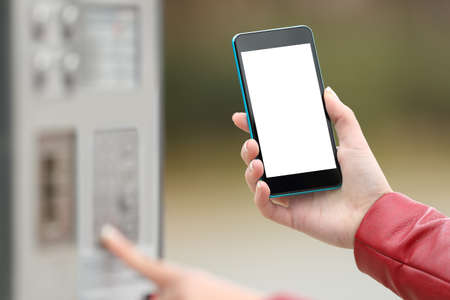 Close up of a girl hands paying with a smart phone and showing a blank screen outdoors on the street
