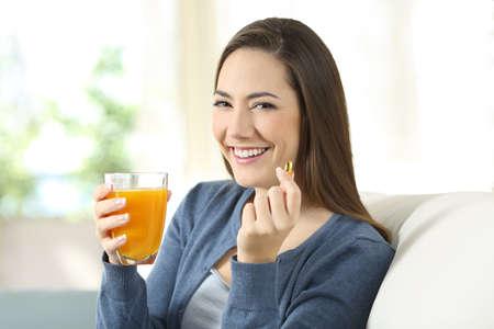 Niña feliz que sostiene un zumo de naranja y una píldora que mira sentado en un sofá en la sala de estar en casa Foto de archivo - 97101457