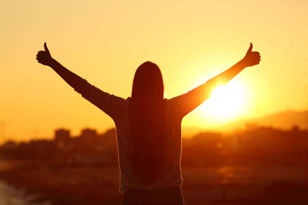 Rückansicht Hintergrundbeleuchtung Silhouette einer Frau Arme mit Daumen nach oben in die Sonne bei Sonnenuntergang