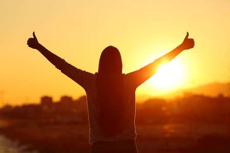 vista trasera vista de fondo silueta de una mujer que levanta los brazos con los pulgares para arriba al sol al atardecer