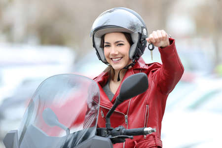 Happy motorbiker showing keys sitting on her new motorbike outdoors on the street