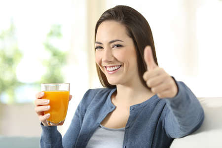 Portrait of a satisfied consumer holding an orange juice glass sitting on a couch in the living room at home