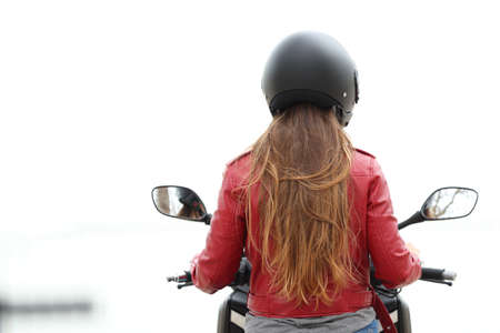 Back view of a motorbiker sitting on a motorcycle on white background Stock Photo