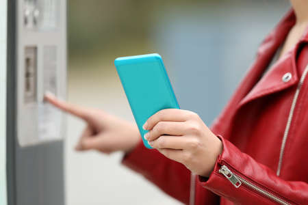 Close up of a girl hands using a smart phone to pay in a payment machine outdoors Фото со стока