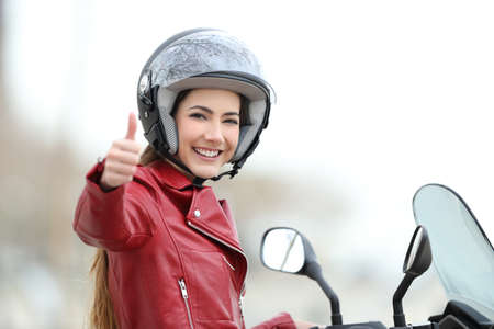 Satisfied motorbiker gesturing thumbs up on her motorcycle outdoors Archivio Fotografico