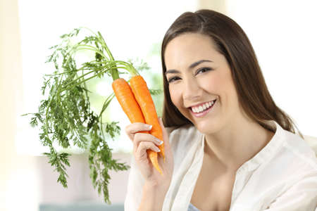 Portrait of a girl showing a bundle of carrots looking at camera sitting on a couch in the living room at home Reklamní fotografie
