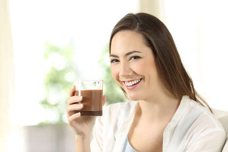 Happy girl holding a cocoa shake looking at you sitting on a couch in the living room at home