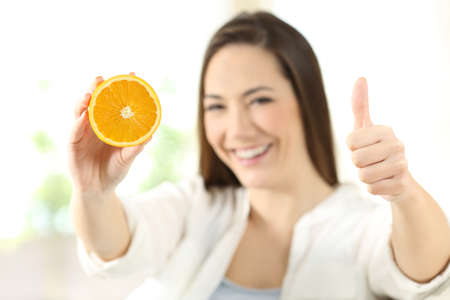Happy woman showing half orange with thumbs up at home Reklamní fotografie