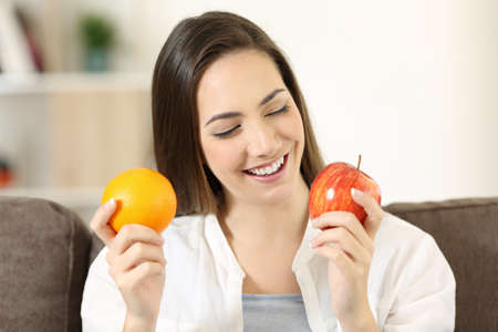 Front view portrait of a happy woman deciding between orange and apple sitting on a couch in the living room at home