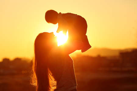 Backlight silhouette of a mother raising her kid son at sunset with the sun in the middle