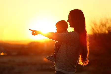 Backlight silhouette of a mother pointing horizon with her baby at sunset Standard-Bild