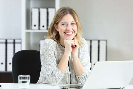 Proud office worker posing laughing and looking at side on a desktop Reklamní fotografie