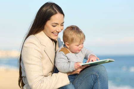 Happy mom teaching and baby learning reading a book on the beach in winter