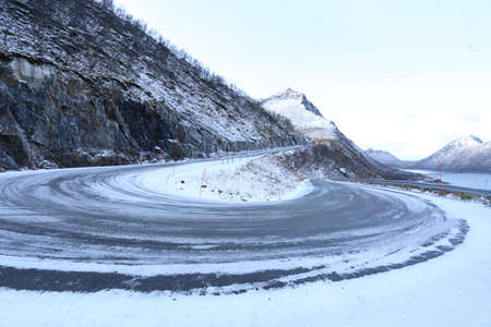 Winter landscape of a snowy dangerous mountain road bend in Norway