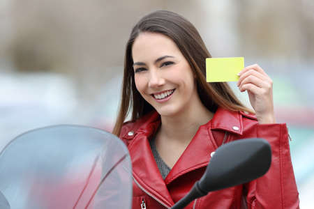 Happy biker showing a credit card or driving license on a motorbike on the street Stock Photo