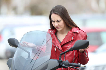 Portrait of a confused biker looking at broken down motorbike on the street