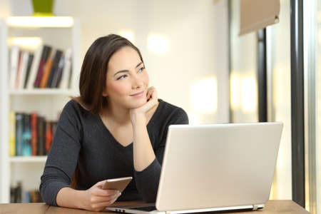Relaxed woman dreaming looking at seide using multiple devices on a table at home