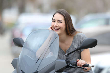 Portrait of a happy biker posing looking at camera on a motorbike on the street Stock Photo - 99648405