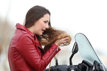 Portrait of a sad biker woman complaining about tangled hair after a motorkike travel