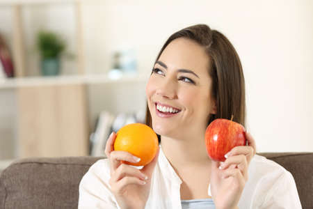 Happy woman wondering about an apple and orange sitting on a couch in the living room at home
