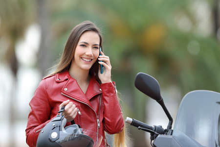 Happy biker calling on smart phone on a motorbike on the street