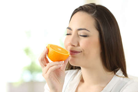 Portrait of a pretty woman smelling half orange at home Stok Fotoğraf - 99039023