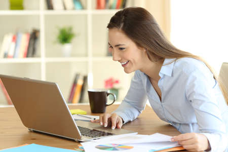Heureux travailleur sérieux travaillant sur la ligne avec un ordinateur portable à la maison Banque d'images - 99039024