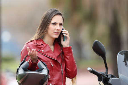 Angry biker on her motorbike calling insurance on phone on the street Stock Photo