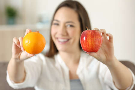 Front view portrait of a happy woman showing two different fruits sitting on a couch in the living room at home Stock Photo