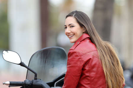 Portrait of a happy biker looking at you on a motorbike on the street