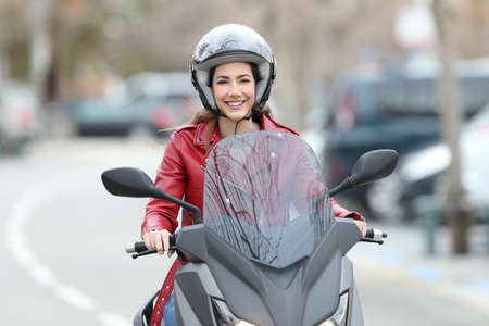 Front view portrait of a happy bker driving a motorbike on the street Stock Photo