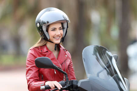 Happy biker sitting on a motorbike looking away on the street Stock Photo