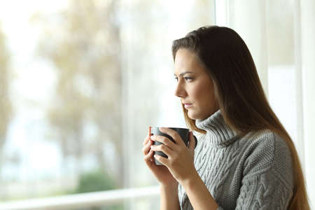 Angry woman looking through a window and holding a mug at home in winter Stock Photo