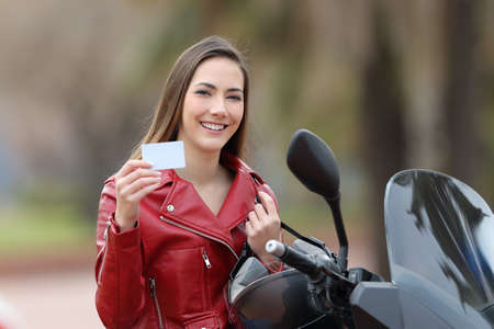 Happy biker girl showing a blank credit card on the street