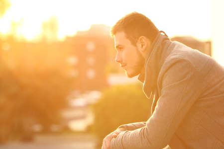 Side view portrait of a serious man looking away in a balcony at sunset in winter