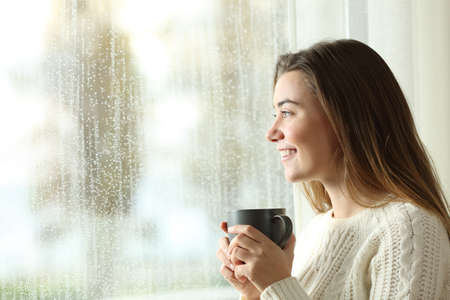 Happy teen holding a mug looking through a window at home in a rainy day Imagens - 99039323