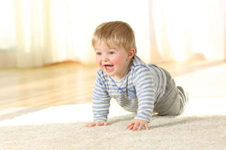Portrait of a cute baby crawling and laughing on the floor at home