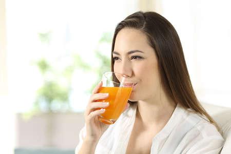 Mujer bebiendo jugo de naranja en un vaso sentado en un sofá en la sala de estar en casa Foto de archivo - 99040030