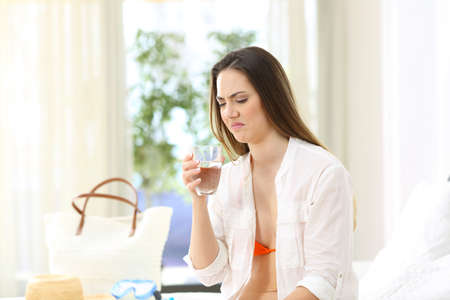 Disgusted woman tasting water with bad flavour in an hotel room on summer vacations