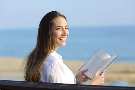 Happy woman holding an open book looking at camera sitting on a bench on the beach