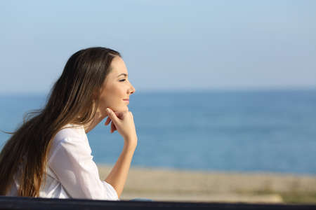 Side view portrait of a pensive woman looking forward on the beach