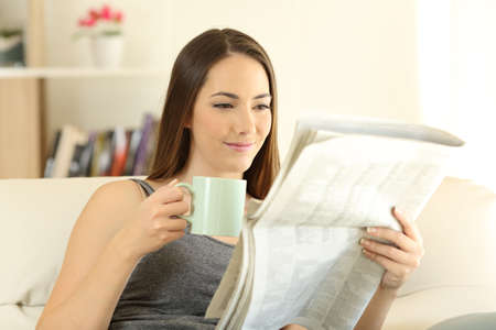 Woman reading a newaspaper in the morning sitting on a couch in the living room at home