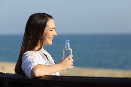 Happy woman holding a water bottle looking at horizon on the beach Stock Photo