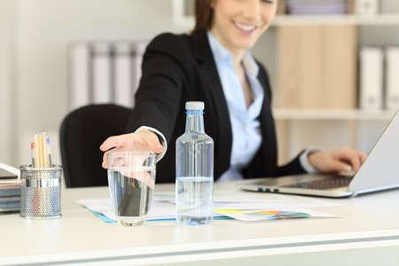 ボトル入り飲料水のグラスに手を伸ばす事務員の手のクローズアップ 写真素材