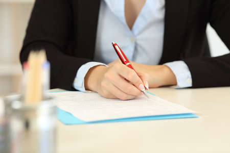 Close up front view of an office worker hands filling form on a desktop Stock Photo