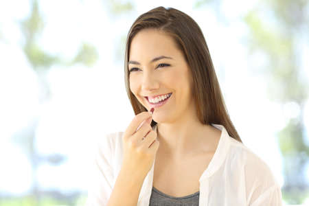 Portrait of a happy woman taking a pill looking away Stock Photo