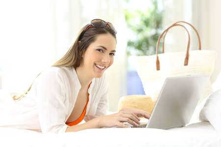 Happy woman using a laptop looking at you lying on a bed of an hotel room on summer vacations